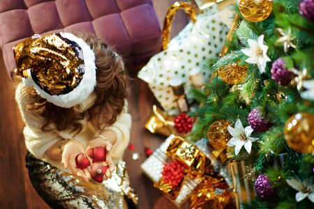 Upper view of stylish middle age housewife with long brunette hair in gold sequin skirt and white sweater under decorated Christmas tree near present boxes holding broken Christmas ball.