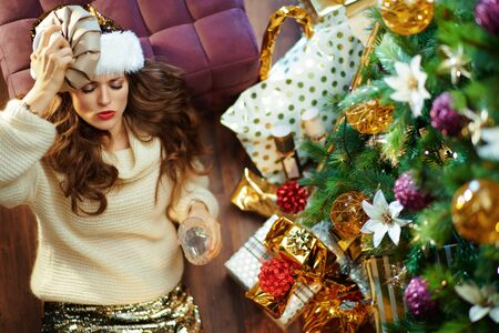 Upper view of stressed elegant middle age woman with long brunette hair in gold sequin skirt and white sweater with glass of water laying on floor under decorated Christmas tree near present boxes.