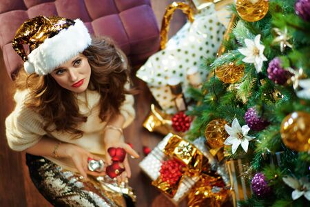 Upper view of unhappy young woman with long brunette hair in gold sequin skirt and white sweater under decorated Christmas tree near present boxes holding broken Christmas ball.