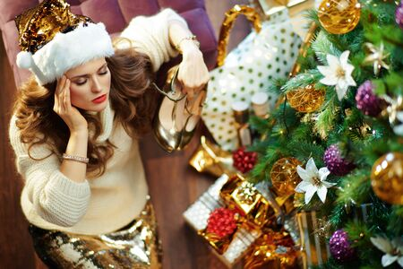Upper view of tired trendy 40 year old woman with long brunette hair in gold sequin skirt and white sweater under decorated Christmas tree near present boxes holding shoes.