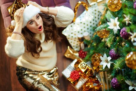 Upper view of shocked modern woman with long brunette hair in gold sequin skirt and white sweater under decorated Christmas tree near present boxes looking at copy space. Reklamní fotografie - 134969976