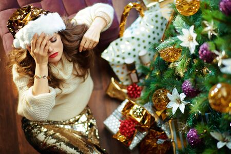 Upper view of stressed stylish 40 year old woman with long brunette hair in gold sequin skirt and white sweater under decorated Christmas tree near present boxes sitting on floor. Reklamní fotografie