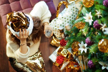 Upper view of stressed stylish woman with long brunette hair in gold sequin skirt and white sweater with glass of water sitting on floor under decorated Christmas tree near present boxes. Reklamní fotografie - 134970285