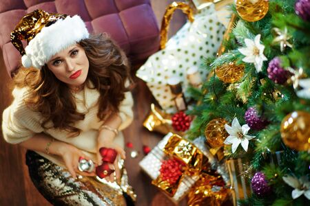Upper view of sad 40 year old housewife with long brunette hair in gold sequin skirt and white sweater under decorated Christmas tree near present boxes holding broken Christmas ball.