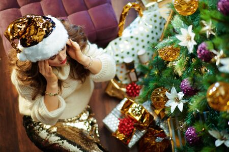 Upper view of stressed stylish woman with long brunette hair in gold sequin skirt and white sweater under decorated Christmas tree near present boxes sitting on floor.