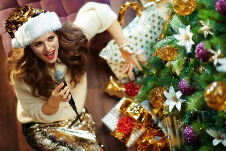 Upper view of happy elegant 40 year old housewife with long brunette hair in gold sequin skirt and white sweater under decorated Christmas tree near present boxes singing into a microphone.