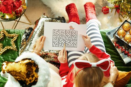 Upper view of elegant mother and child sitting on couch in the modern living room at Christmas playing maze games. Stock Photo