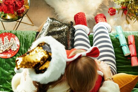 Upper view of modern mother and child sitting on divan in the modern living room at Christmas hugging.