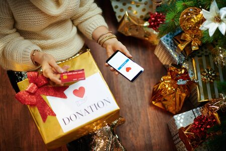 Stylish housewife in gold sequin skirt and white sweater with credit card making donation via smartphone application under decorated Christmas tree near present boxes.