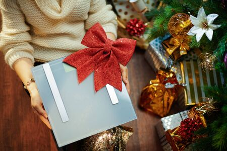 Closeup on concerned trendy woman in gold sequin skirt and white sweater showing scales with red bow under decorated Christmas tree near present boxes.