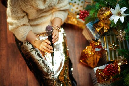 Closeup on elegant 40 year old housewife in gold sequin skirt and white sweater under decorated Christmas tree near present boxes singing into a microphone.