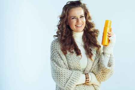 happy stylish housewife with long wavy hair in neck sweater and cardigan with suntan lotion isolated on winter light blue.