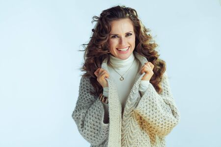 Portrait of smiling elegant housewife with long wavy hair in neck sweater and cardigan against winter light blue background. 免版税图像