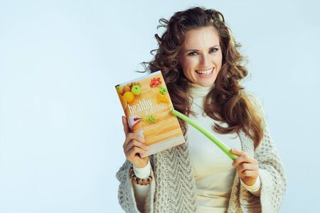 smiling elegant female with long wavy hair in neck sweater and cardigan with healthy eating book and celery on winter light blue background.