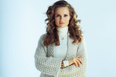 Portrait of elegant housewife with long wavy hair in neck sweater and cardigan isolated on winter light blue background.
