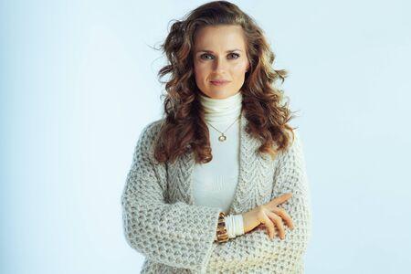 Retrato de ama de casa elegante con pelo largo ondulado en suéter de cuello y chaqueta de punto aislado sobre fondo azul claro de invierno.