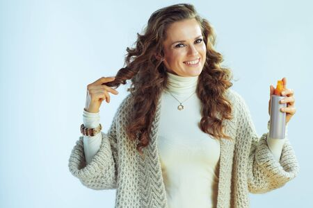 smiling elegant housewife with long wavy hair in neck sweater and cardigan with hair product isolated on winter light blue background.
