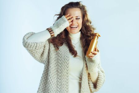 smiling young housewife with long wavy hair in neck sweater and cardigan holding self tanning lotion isolated on winter light blue. 스톡 콘텐츠