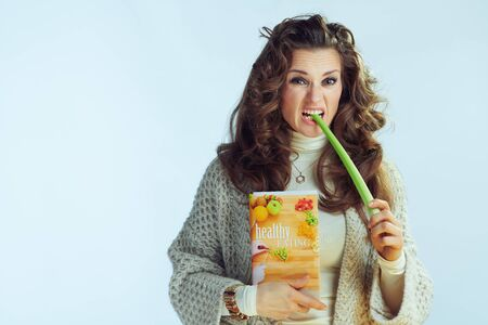 unhappy young housewife with long wavy hair in neck sweater and cardigan with healthy eating book eating celery isolated on winter light blue background.
