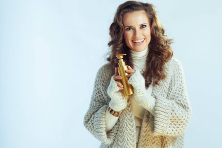 Portrait of smiling elegant 40 year old woman with long wavy hair in neck sweater and cardigan with self tanning lotion isolated on winter light blue.