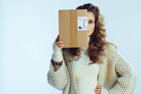modern female with long wavy hair in neck sweater and cardigan holding parcel in the front of face on winter light blue background. Foto de archivo