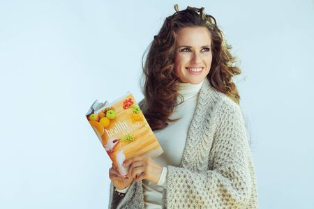 smiling young woman with long wavy hair in neck sweater and cardigan with healthy eating book looking at copy space on winter light blue background. Banque d'images