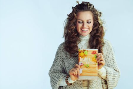 happy elegant female with long wavy hair in neck sweater and cardigan holding healthy eating book isolated on winter light blue.