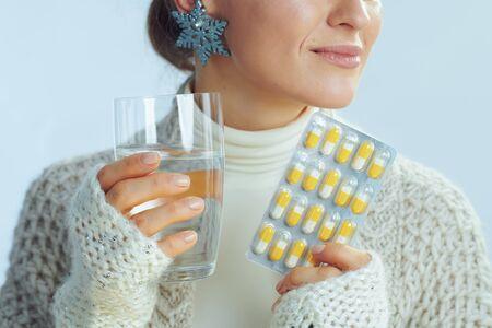Nahaufnahme auf glückliche elegante Frau in Rollkragenpullover und Strickjacke mit Glas Wasser und Blisterpackung mit Vitaminen einzeln auf hellblauem Winterhintergrund.