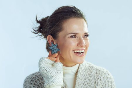 smiling stylish 40 years old woman in roll neck sweater and cardigan with snowflake earring looking at copy space on winter light blue background. Archivio Fotografico