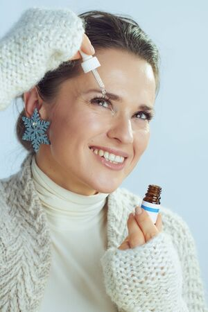 smiling elegant 40 years old woman in roll neck sweater and cardigan with snowflake earring using eye drops as winter eye care against winter light blue background.