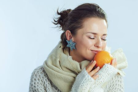 modern woman in roll neck sweater and cardigan enjoying orange against winter light blue background.