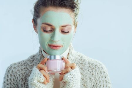 modern woman in roll neck sweater and cardigan with green facial mask holding cosmetic jar isolated on winter light blue.