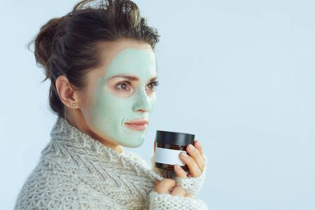 stylish woman in roll neck sweater and cardigan with green facial mask holding cosmetic jar looking at copy space isolated on winter light blue.
