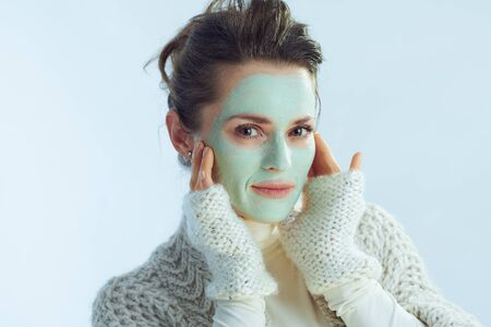Portrait of modern 40 years old woman in roll neck sweater and cardigan with green facial mask touching face isolated on winter light blue background. Reklamní fotografie