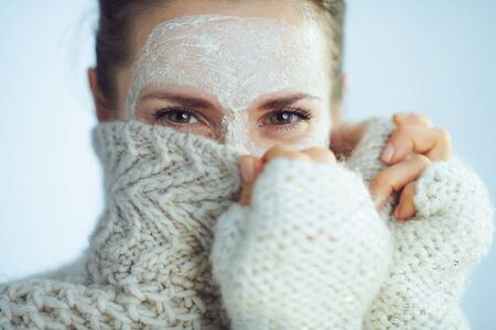 elegant woman in roll neck sweater and cardigan with white facial mask hiding behind clothes on winter light blue background.