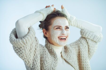 relaxed stylish woman in roll neck sweater and cardigan with white facial mask as part of winter skin care looking at copy space on winter light blue background.