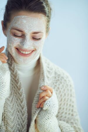 smiling modern middle age woman in roll neck sweater and cardigan with white facial mask as part of winter skin care on winter light blue background.