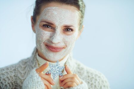 smiling elegant middle age woman in roll neck sweater and cardigan with white facial mask showing snowflake against winter light blue background.