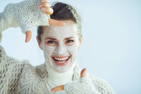 smiling elegant woman in roll neck sweater and cardigan with white facial mask framing with hands on winter light blue background.