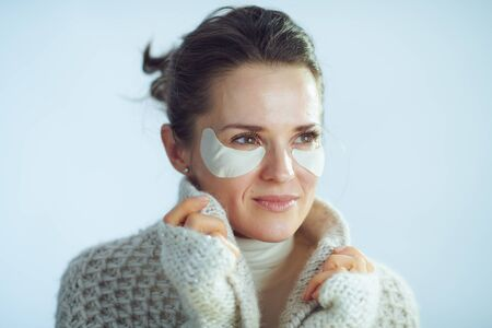40 years old housewife in roll neck sweater and cardigan with cosmetic eye patches as part of winter skin care covering in clothes looking into the distance isolated on winter light blue background.