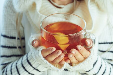 Closeup on stylish middle age woman in white striped sweater, scarf and ear flaps hat holding cup of hot tea with lemon and honey against winter light blue background.