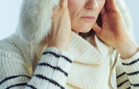 Closeup on stressed stylish 40 years old woman in white striped sweater, scarf and ear flaps hat against winter light blue background.