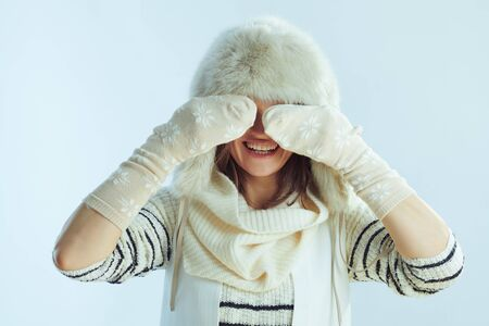 happy middle age woman in white striped sweater, scarf and ear flaps hat playing with winter socks isolated on winter light blue background. Banco de Imagens