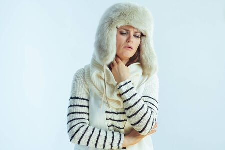 elegant woman in white striped sweater, scarf and ear flaps hat having neck ache on winter light blue background.