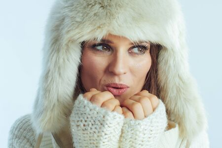 Portrait of stylish female in white striped sweater, scarf and ear flaps hat warming hands with breathing on winter light blue background.