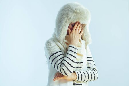 stressed modern female in white striped sweater, scarf and ear flaps hat on winter light blue background. Banco de Imagens