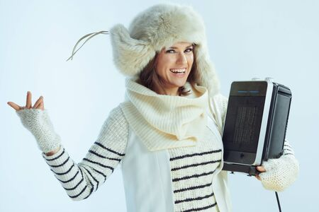 Portrait of smiling stylish woman in white striped sweater, scarf and ear flaps hat holding portable electric heater on winter light blue background.