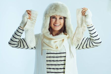 Portrait of happy stylish woman in white striped sweater, scarf and ear flaps hat showing winter socks against winter light blue background.