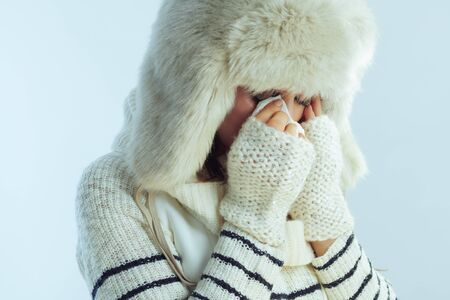 stressed stylish woman in white striped sweater, scarf and ear flaps hat crying and wiping eyes with napkin on winter light blue background.