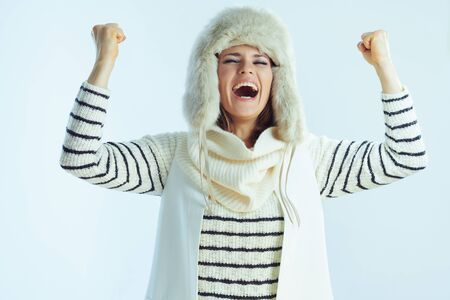 smiling stylish middle age woman in white striped sweater, scarf and ear flaps hat with raised arms rejoicing isolated on winter light blue background. Stock fotó